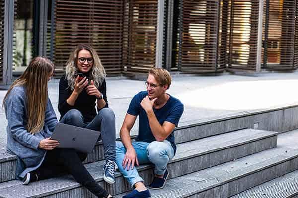 Maestrías mejor pagadas - 2 mujeres y 1 hombre, jovenes, estudiantes con un laptop sentados en unas escalas