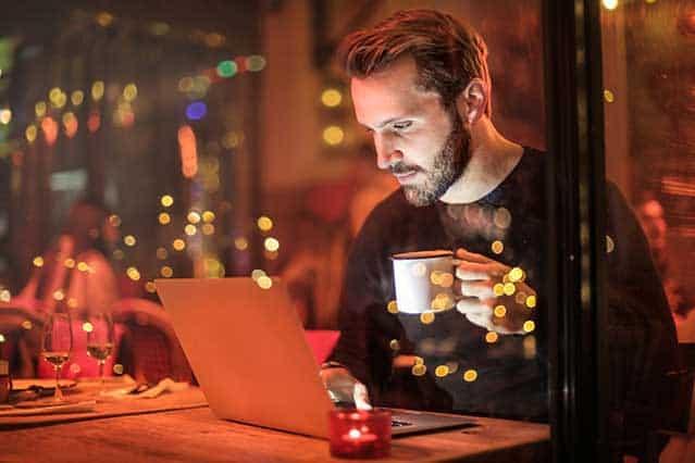 estudiar un posgrado - hombre, estudiando en su portátil sosteniendo una taza de cafe