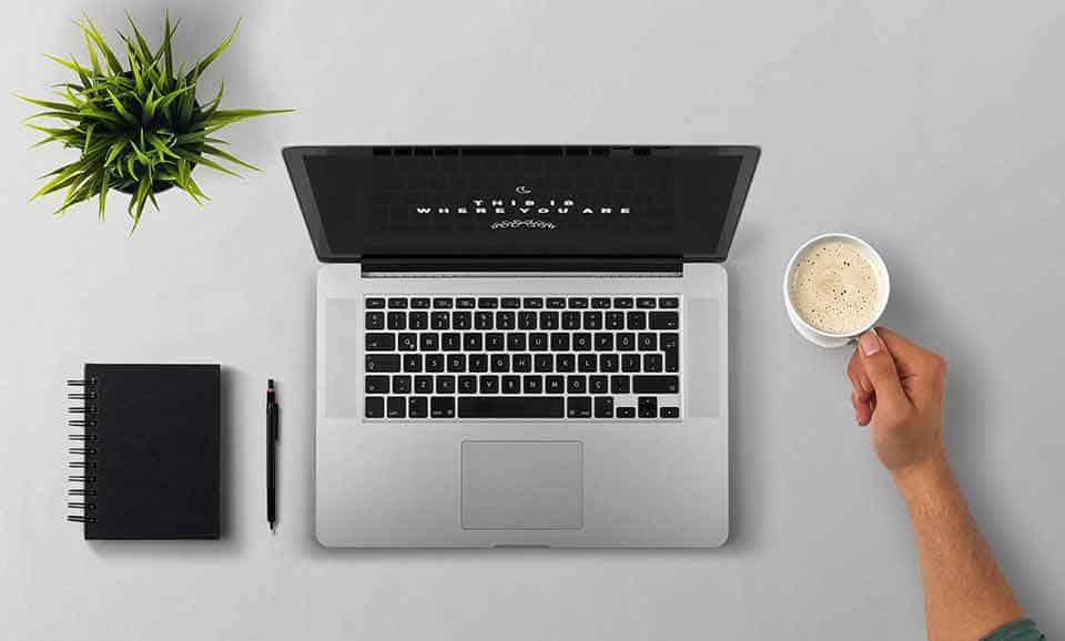 las mejores maestrias online - laptop, cafe, agenda sobre escritorio