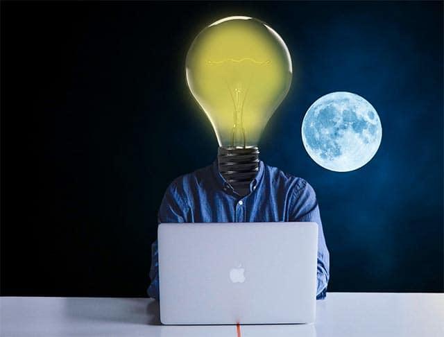 MBA a distancia en España - hombre con cabeza de bombillo frente a un ordenador