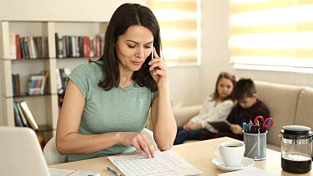 maestria a distancia - madre al telefono y estudiando, mientras esca con los niños