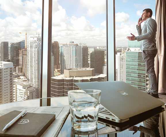 maestria a distancia - Profesional al telefono, en una oficinas con vistas a la ciudad
