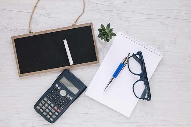 Útiles de oficina (una pizarra, una calculadora, una agenda y lentes) que utilizan los administradores. En el Día Internacional del Administrador celebramos que sean profesionales multifacéticos. ¡Celebra el Día Internacional del Administrador!