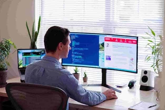 Chico en un computador indagando sobre los factores más importantes para estudiar maestrias virtuales en Colombia 2021.