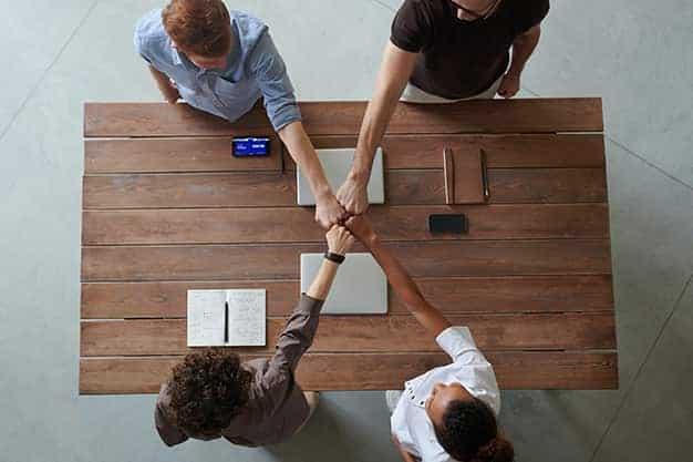 Se observan unos jóvenes que unen los puños en señal de equipo. Entre los pasos y requisitos para crear una empresa, está implícita la necesidad de un equipo sólido para poner en marcha la empresa. Lee más sobre los pasos y requisitos para crear una empresa aquí.