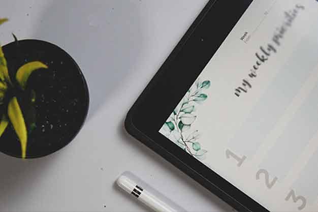 Una persona que estudia maestrías económicas virtuales y revisa en su tablet el planeador semanal para organizar las clases de las maestrías económicas virtuales. La autodisciplina y la organización son aptitudes claves para un buen desempeño en las maestrías económicas virtuales.