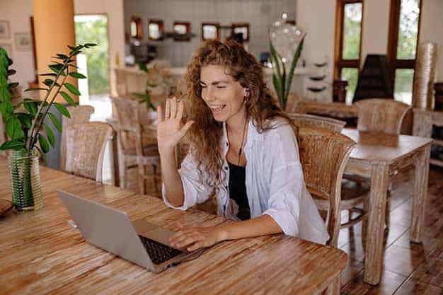 Se observa una mujer frente a una laptop, saludando porque estudia Maestrías virtuales en Argentina 2021 o el mundo. Las Maestrías virtuales en Argentina o el extranjero te abren oportunidades increíbles para hacer carrera en el extranjero. ¡Apuesta por las Maestrías virtuales en Argentina 2021 o el mundo!