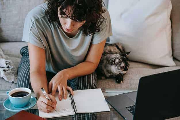 Se observa una estudiante frente a una laptop, apuntando contenido adquirido de nuestras maestrías en línea con beca barata; junto a ella un gato. Las maestrías en línea con beca barata forman profesionales más preparados. Las maestrías en línea con beca barata son el futuro.