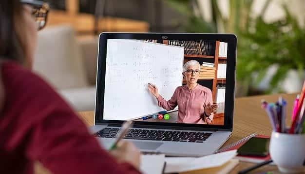 En la imagen podemos ver a una joven profesional, tomando una clase en una escuela de administración y de empresas en línea.