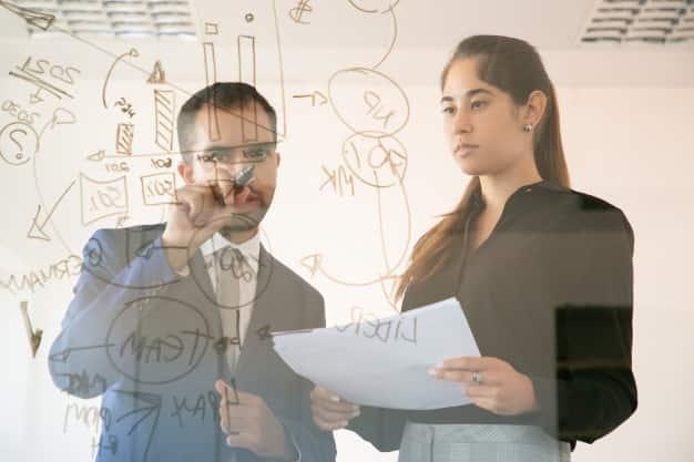 Dos profesionales están creando una nueva estratagia organizacional, aplicando lo aprendido al estudiar administración y dirección de empresas. El conocimiento adquirido al estudiar administración y dirección de empresas, te dotará de grandes habilidades.