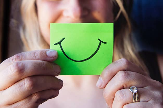Una joven sostiene un dibujo de una cara sonriente porque acaba de finalizar su formación sobre las funciones del director de recursos humanos en una empresa. Ella realizó una maestría en línea, en donde aprendió mucho más de las funciones del director de recursos humanos en una empresa.
