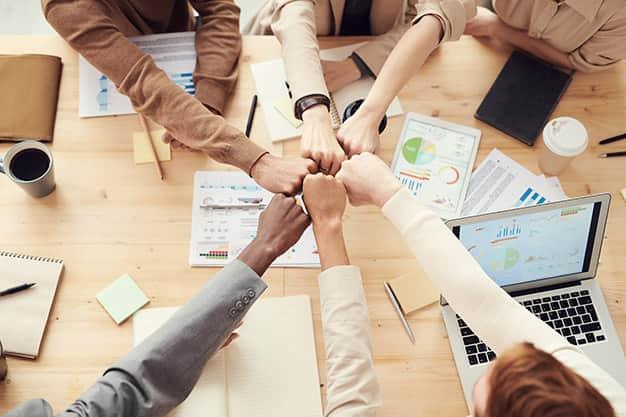 Vemos a un grupo de trabajo celebrar el final de una jornada exitosa, las funciones del director de recursos humanos en una empresa aplicadas correctamente han hecho que se posicionen alto en el mercado laboral. El profesional que ejerció sus funciones del director de recursos humanos en una empresa, contrató a un gran equipo.