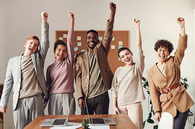 En la imagen cuatro personas celebran una buena jornada después de hablar sobre las funciones del director de recursos humanos en una empresa. La nueva persona a cargo empezará a aplicar las funciones del director de recursos humanos en una empresa con su nuevo equipo de trabajo