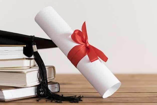En esta fotografía se ve un diploma y gorro de graduado de una escuela de administración y de negocios en línea.
