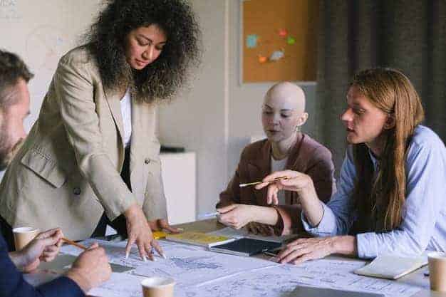 Al estudiar un MBA en línea en España, aprenderas con profesionales del sector. En la imagen, se ve una chica explicando a otras personas que van a estudiar un mba en línea en España, los secretos del sector.