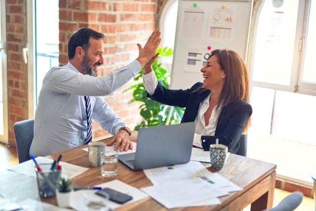 Dos personas celebran los resultados de su empresa, gracias a lo aprendido en una escuela internacional de negocios en Colombia. Gracias a la escuela internacional de negocios en Colombia, hicieron realidad sus sueños.