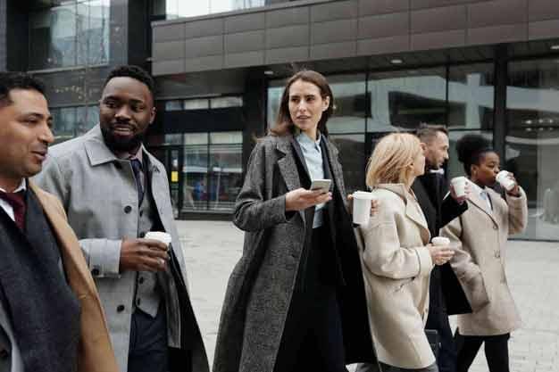 En la imagen vemos a los trabajadores de una empresa caminando por la calle; hablan sobre los beneficios de estudiar en una escuela internacional de negocios en Colombia. Una joven del grupo está interesada en ingresar a una escuela internacional de negocios en Colombia.