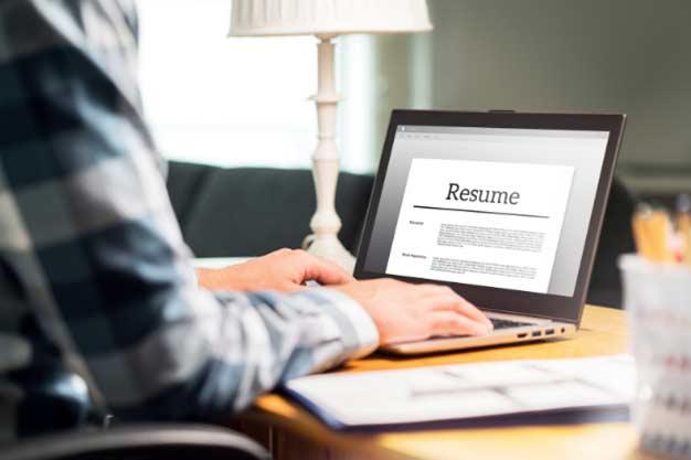 Se ve a un profesional actualizando su CV para obtener ofertas de empleo en el extranjero. Él busca adaptar su Curriculum para tener oportunidad de conseguir ofertas de empleo en el extranjero.